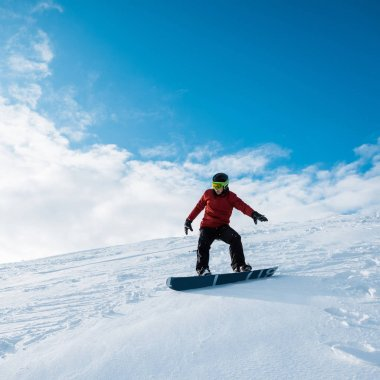 Snowboarder in helmet riding on slope against blue sky stock vector