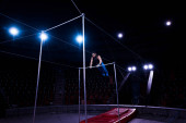 Photo handsome gymnast performing on horizontal bars in circus