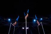 Photo low angle view gymnasts performing on horizontal bars in arena of circus