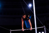 Photo handsome gymnast performing on horizontal bars in arena of circus