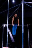 szelektív fókusz jóképű és erős tornász teljesítő horizontális bárok arénában cirkusz