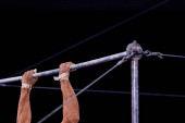 Photo cropped view of athletic gymnast performing on horizontal bars in circus