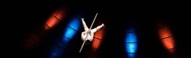 panoramic shot of acrobat balancing on pole in arena of circus