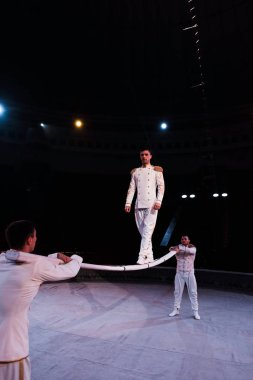 acrobats supporting handsome man walking on metallic pole in circus