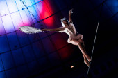 vonzó légi akrobata holding ütő, miközben álló kötél