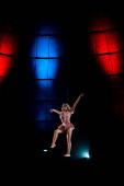 artistic aerial acrobat gesturing while performing in circus