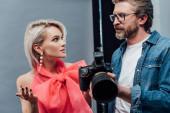 schöner Art Director hält Digitalkamera in der Hand und betrachtet attraktives Modell