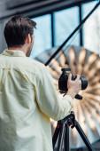 Photo back view of photographer touching digital camera on tripod