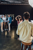 selective focus of photographer taking photo of man sitting on chair in photo studio