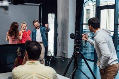 Selective focus of makeup artist near model and art director stock vector