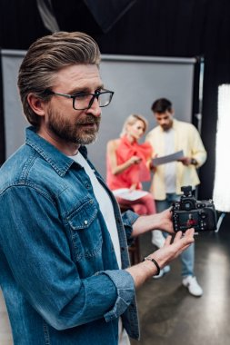 Selective focus of bearded art director in glasses pointing with hand at digital camera stock vector