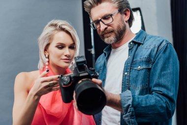 Handsome art director holding digital camera near attractive model stock vector
