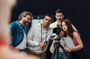 Selective focus of happy art director near coworkers and digital camera in photo studio stock vector