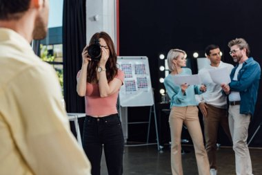 Selective focus of photographer taking photo of model near colleagues stock vector