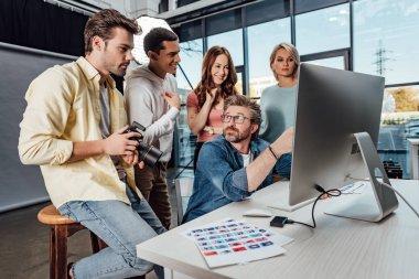 Selective focus of creative director looking at happy assistants in photo studio stock vector