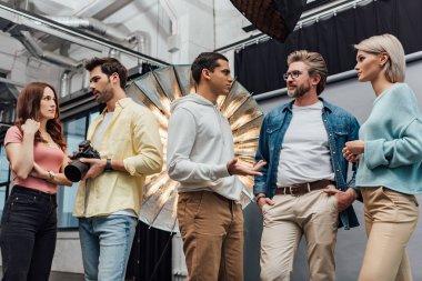 Art director standing with hands in pockets near coworkers in photo studio stock vector
