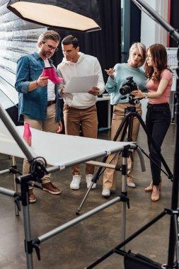 Art director holding pink shoe near assistant in photo studio stock vector