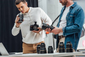 Ausgeschnittene Ansicht eines bärtigen Art Directors mit Fotoobjektiv in der Nähe eines Fotografen