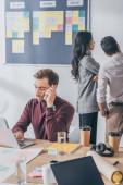 selektivní zaměření podnikatel mluví na smartphone v blízkosti skrum mistrů