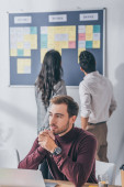 selective focus of handsome scrum master with clenched hands near coworkers