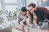 šťastný multikulturní podnikatelé a podnikatelky při pohledu na notebook v kanceláři