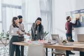 veselé multikulturní podnikatelek v blízkosti podnikatele a gadgets v úřadu