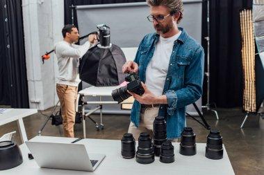 Bearded photographer holding digital camera near laptop on table stock vector