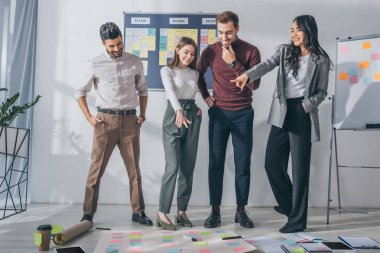 Happy multicultural scrum masters looking at sticky notes on floor stock vector
