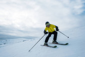 sportovec drží lyžařské hole při lyžování na bílém sněhu