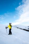Lyžař s lyžařskými hole stojící na bílém sněhu venku