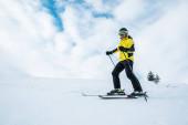 atletický muž v helmě a brýlích lyžování na sjezdovce v zimním období