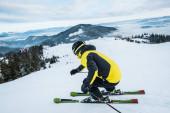 Sportler mit Helm beim Skifahren in den Bergen