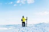 lyžař v helmě drží lyžařské hole a stojí na sněhu proti modré obloze