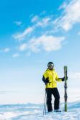 Fotografie  Skifahrer mit Skibrille hält Skistöcke in der Hand und steht auf Schnee vor blauem Himmel