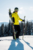Fotografie Skifahrer hält Ski und steht vor blauem Himmel in den Bergen