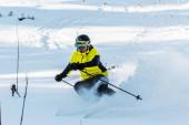 Fotografie Skifahrer mit Helm hält Skistöcke beim Skifahren auf weißer Piste