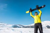 Glücklicher Sportler im Helm hält Snowboard über Kopf