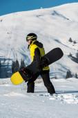 Fotografie boční pohled na snowboardista v helmě procházky v horách se snowboardem
