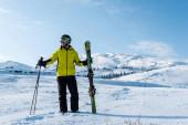 lyžař v helmě a brýlích s klacky na bílém sněhu v horách