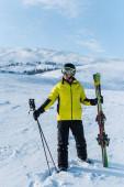 Skifahrer mit Helm steht mit Stöcken auf weißem Schnee in den Bergen