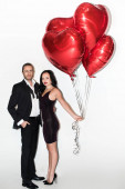 Fényképek beautiful happy couple holding red heart shaped balloons on valentines day on white