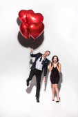 excited couple holding red heart shaped balloons on valentines day on white