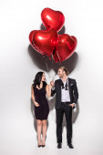 smiling couple holding red heart shaped balloons on valentines day on white