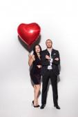 usmívající se pár drží červené srdce ve tvaru balónku na Valentýna na bílém