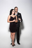 beautiful couple in suit and dress holding champagne glasses for valentines day on white