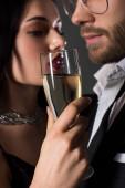 Selektiver Fokus eines schönen Paares mit einem Glas Champagner am Valentinstag, isoliert auf grau