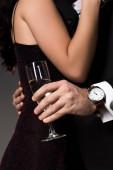 Teilansicht des Paares, das sich umarmt und ein Glas Champagner in der Hand hält, isoliert auf grau