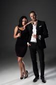 krásný mladý pár s sklenicemi šampaňského na Valentýna na šedé