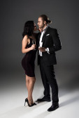 junges Paar mit Champagnergläsern zum Valentinstag auf grau