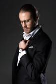 pohledný elegantní muž v obleku a kravatu luk izolované na šedé
